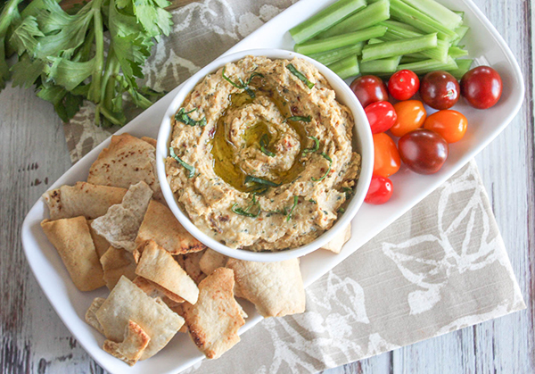 A view looking down at the compted hummus on a plate with chips fresh tomatoes and celery