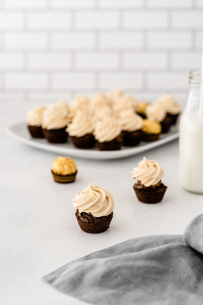 frosted ferrero rocher brownie bite with platter of brownies in the background and jar of milk