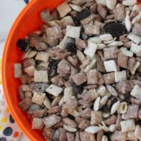 orange bowl full of mixed cookies and cream chex mix and oreo cookies