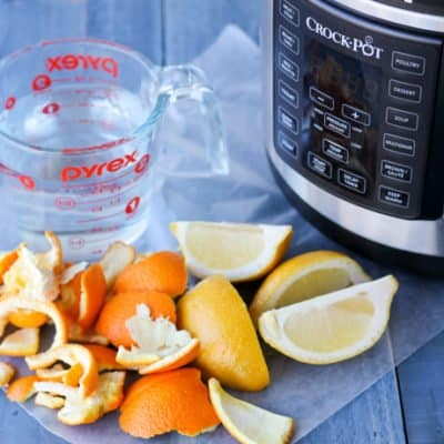 How to remove cooking odors: orange rinds, lemons, cleaning solution and Crockpot Express on a table