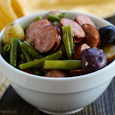 green beans, purple potatoes and sliced sausage in a bowl
