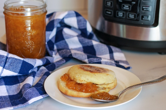 English muffin on white plate with peach jam spread; Crockpot Express in background