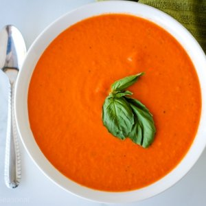 top down view of bowl of roasted red pepper and tomato soup