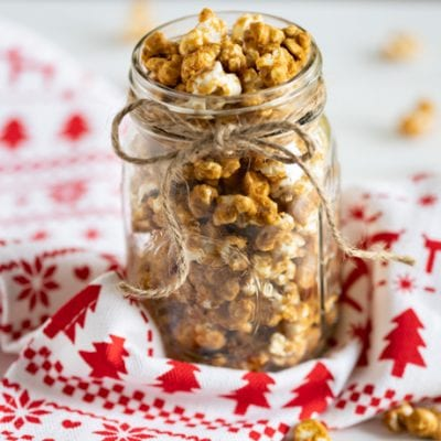 gingerbread caramel corn in a glass jar on a Christmas towel