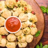 cooked garlic butter pizza monkey bread on a wooden platter