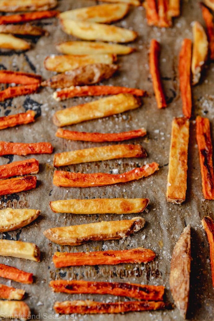 baked carrot fries and potato fries on a baking sheet