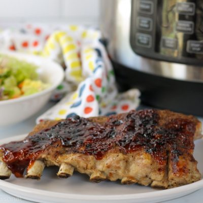 cooked rack of ribs with crockpot express in the background