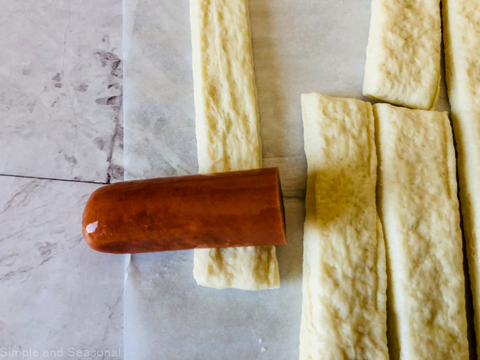 hot dog piece being wrapped up in a strip of dough