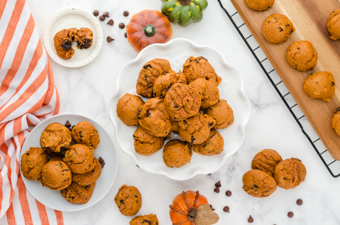 top down view of table with platter, plate and tray of pumpkin cookies