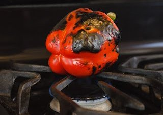 A red pepper cooking over a gas stove flame