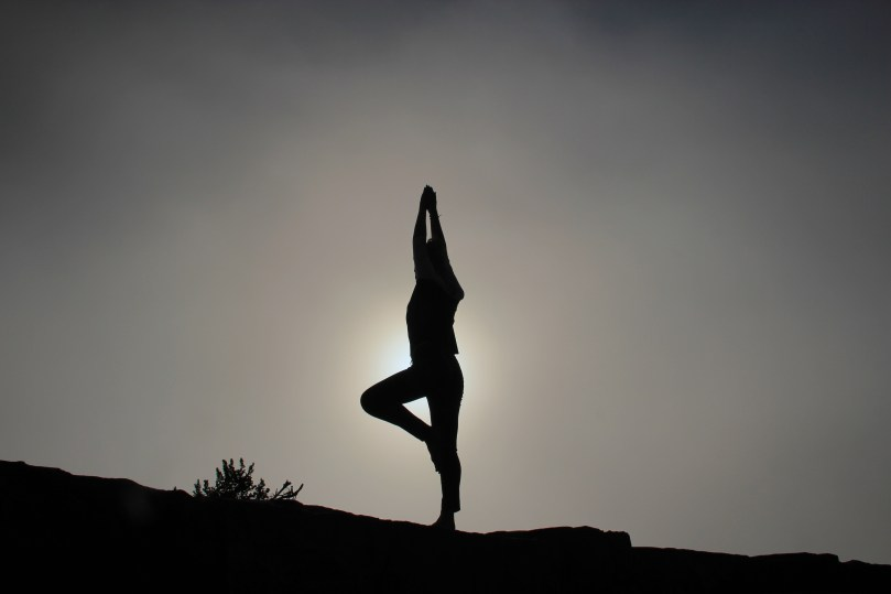 woman doing yoga on hill at sunset