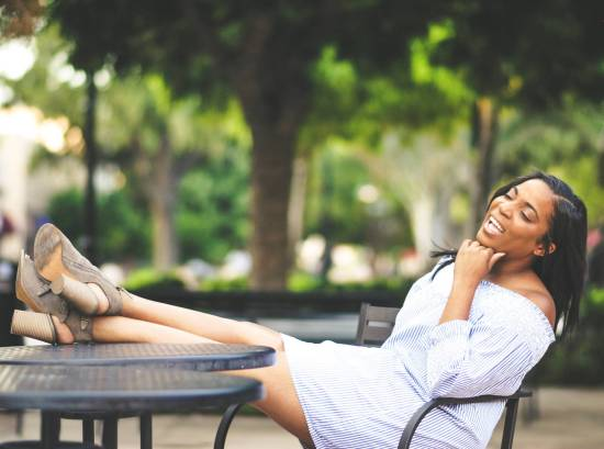 Black woman practicing self care with her feet up on table and smiling