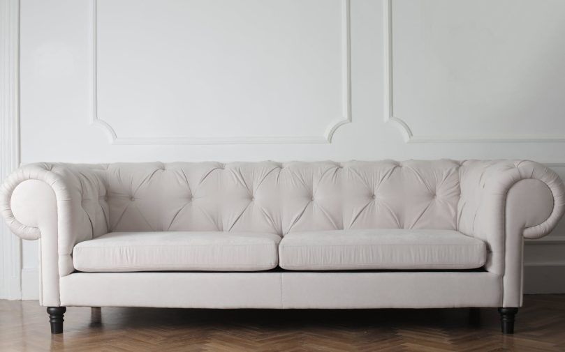 cream couch in front of white wall