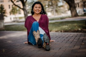 Girl sitting on the ground with cowboy boots with 2018 written in chalk.