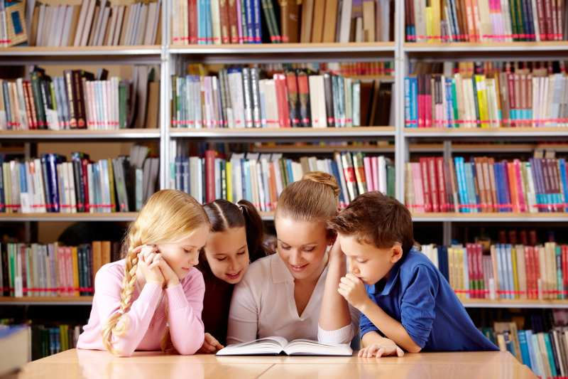 Teacher and children in a primary school library reading from resources found via a library system