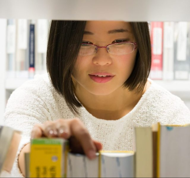 Woman choosing a book in a library