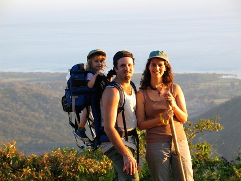 Photograph of a man, woman and child on a hilltop hike with the Pacific Ocean in the background.