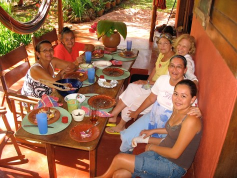 Six ladies gathered around a table on a shaded porch. Their plates are mostly empty.