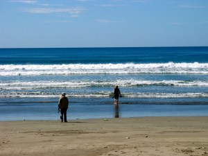 Photo of a couple on the beach, a woman wading into the ocean and a man standing at the waves edge.