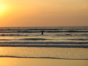 Photo of someone, arms raised, wading waist deep in small ocean waves at sunset.