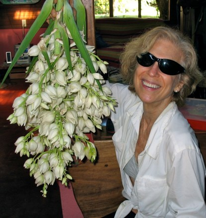 Photo of a woman holding up a harvested Yucca Flower plant, aka flor de Itabo