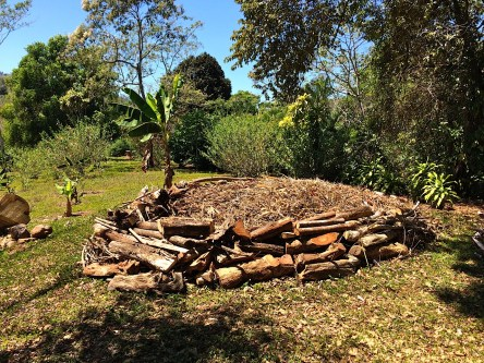 A photo of a large composting circle built with logs containing tree and plant trimmings in the open sun