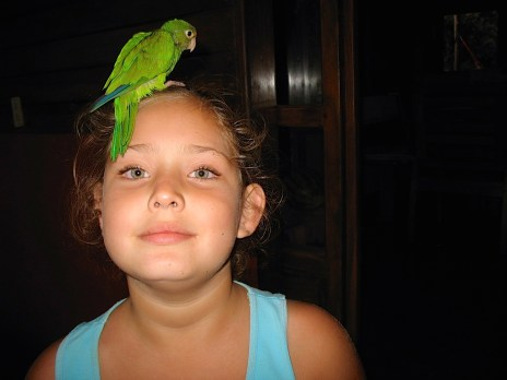 Photo of a young girl with a pet parakeet perched on her head