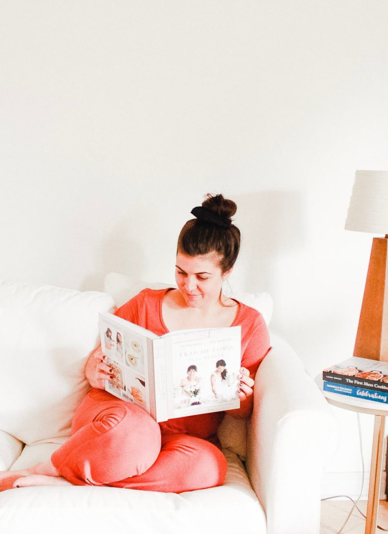 woman reading cookbook on couch