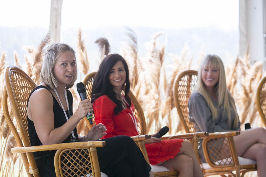 Three women sitting on stage with microphone Panelist Karen Menez, Tori Wesszer and Eva Redpath