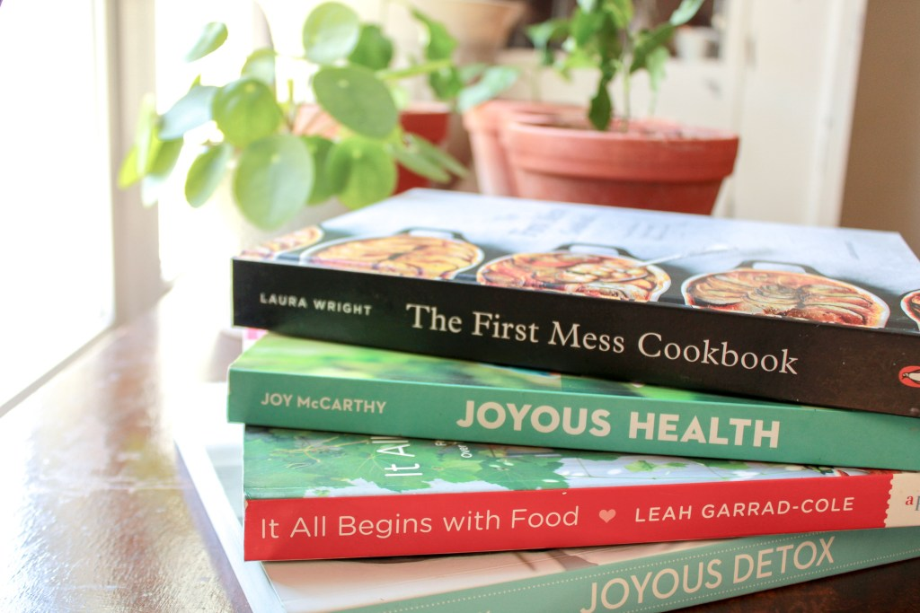 Stack of cookbook including The First Mess Cookbook and Joyous Health