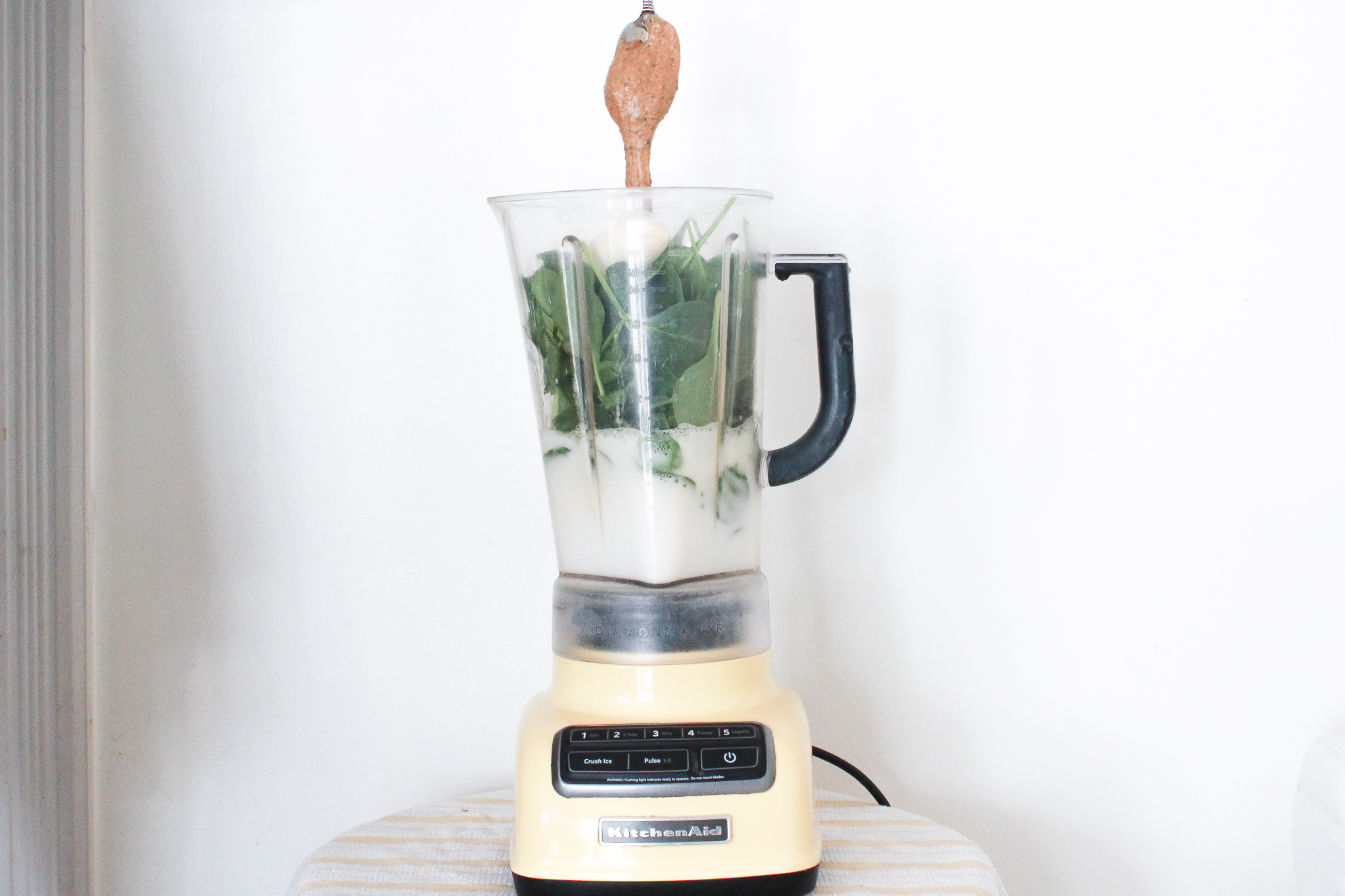adding spoonful of almond butter to green smoothie in blender