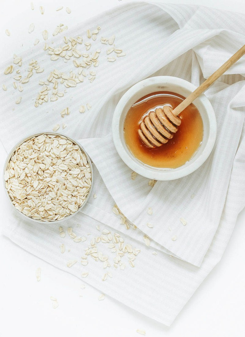 honey and oats in white bowls for making DIY Face Masks
