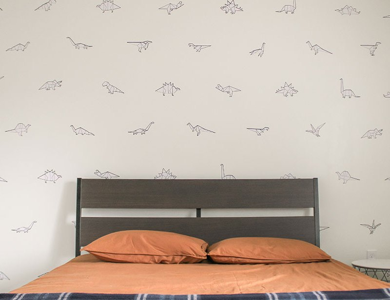 Boys Bedroom with Paper Dinos decals on white wall behind wood bed