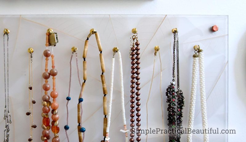a resin panel with hooks holding necklaces