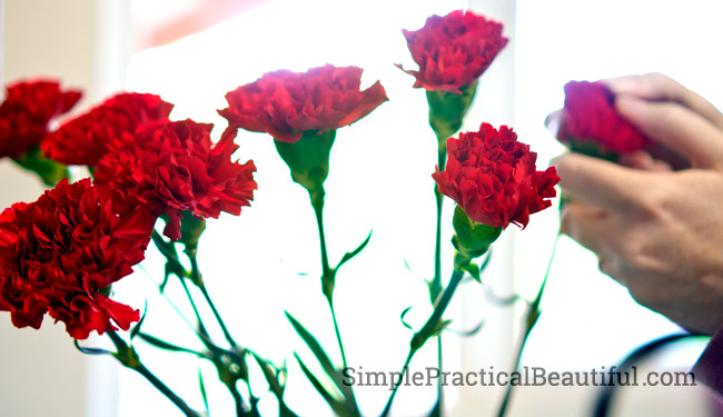 A patriotic DIY centerpiece with blue and white vases and red carnations