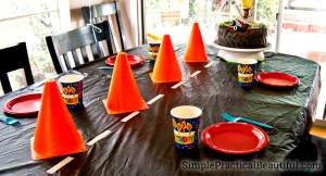 Monster truck birthday party decorations, including cones and a road tablecloth