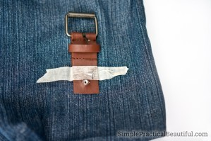 The end of a belt being used to make a purse clasp for a repurposed jeans purse
