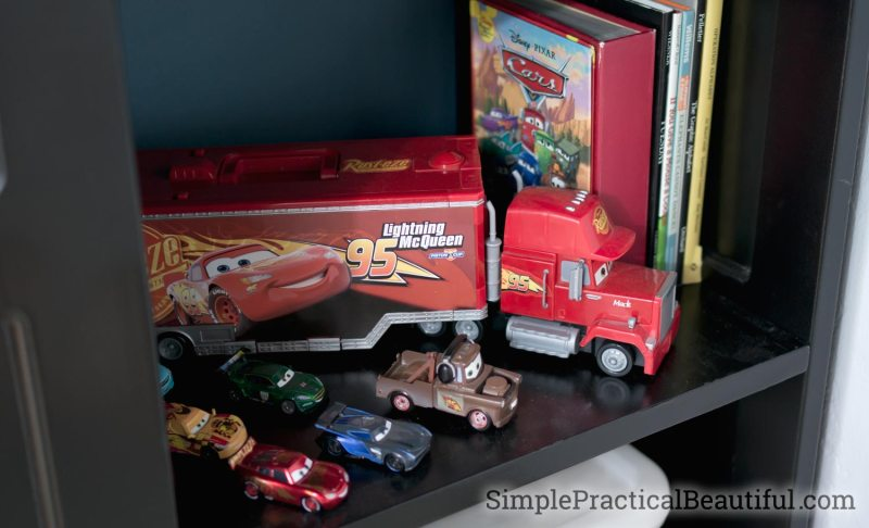 A loft bed refinished in black with a shelf dedicated to Lightning McQueen and all his friends from the Disney Pixar Cars Movie
