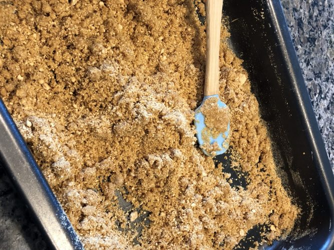 spatula with graham cracker crumbs in pan making magic bars