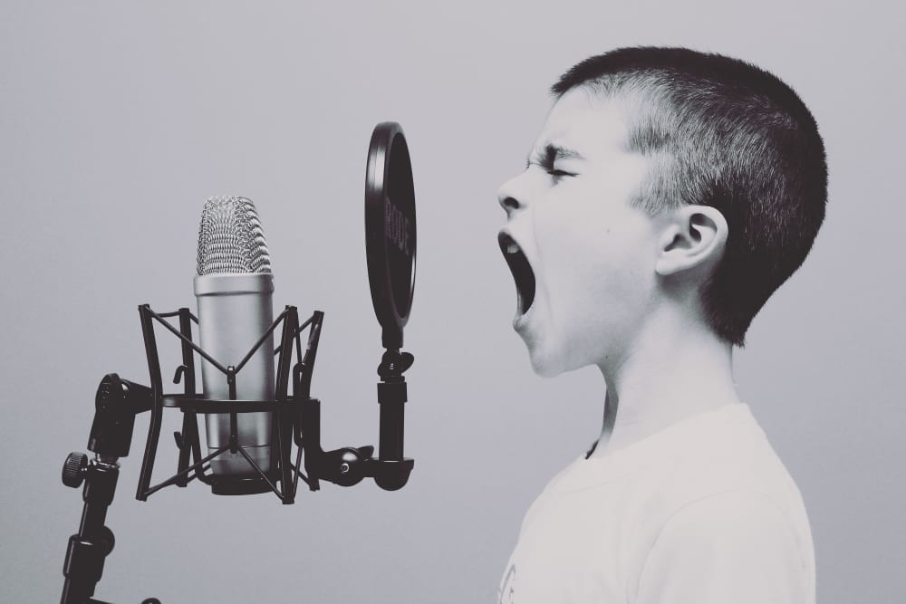 Grayscale profile of boy with buzzcut and mouth wide open screaming into a microphone