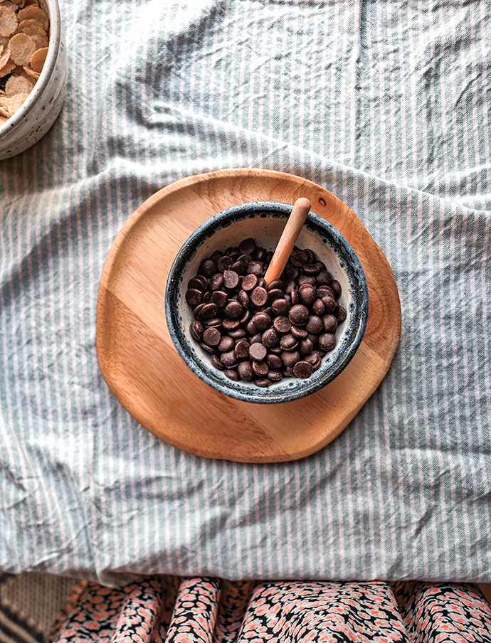 Wooden plate with dark chocolate dairy free chocolate chips on a blue towel