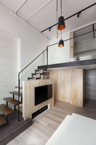 The color palette of light woods, white walls, and black fixtures carries through on both levels.