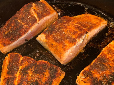 cooked pieces of salmon in pan