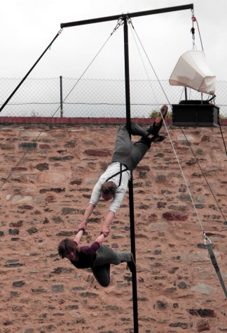 A man hanging on rod carrying woman