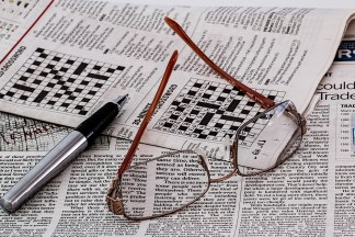 Reading glasses and a pen lay on a newspaper with half-solved crossword