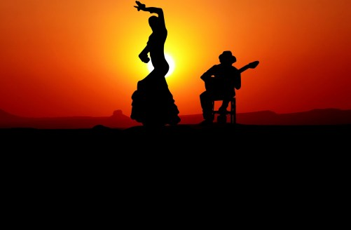 A woman dancing flamenco outdoor at sunset while a man sitting on a chair plays the guitar