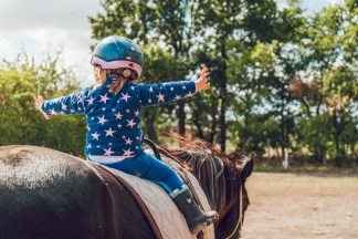 A little kid riding a horse wearing a helmet