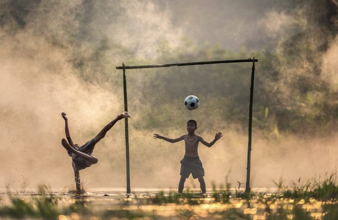 Kids playing soccer on a misty swamp