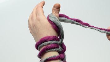 Den Arbeitsfaden von vorne nach hinten zwischen die Hand und den ausgestreckten Daumen legen und locker festhalten.