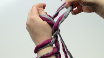 … und über die komplette Hand ziehen, dabei den Arbeitsfaden locker festhalten.